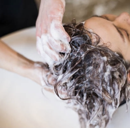 Young male hair stylist is shampooing female hair